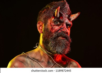 Halloween holiday celebration, cosplay. Man demon on black background. Satan with beard,