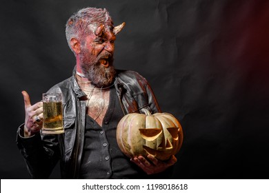 Halloween holiday celebration and party. Man with satan horns hold pumpkin. Bad habits and addiction concept. Hipster demon drink beer on black background. Devil happy smile with glass mug.
