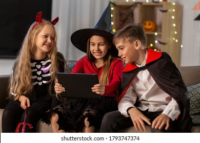 halloween, holiday and childhood concept - smiling boy and girls in party costumes of witch, dracula and devil with tablet pc computer at home