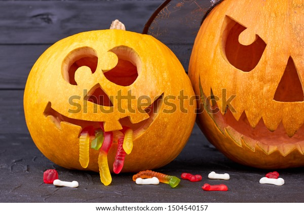 Halloween holiday composition. Funny Halloween pumpkins with jelly worms in mouth. Halloween, junk food and confectionery concept.