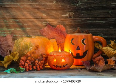 Halloween holiday composition. Ripe pumpkin, mug with face, dry maple leaves and light rays on the old wooden background