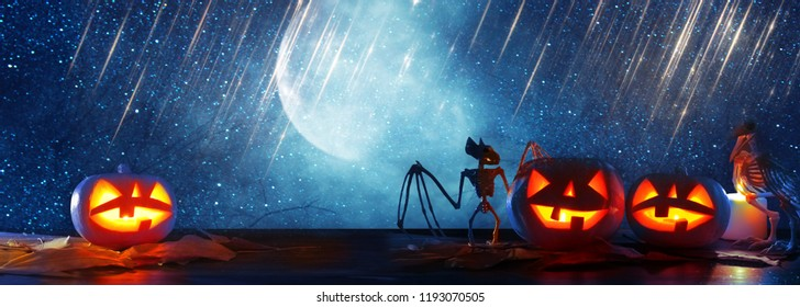Halloween holiday concept banner. Pumpkins over wooden table at night scary, haunted and misty forest