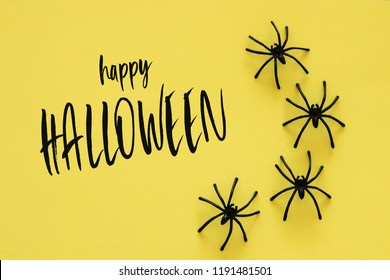 Halloween holiday concept. Black spiders over yellow background. Top view, flat lay