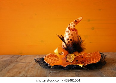 Halloween holiday concept. Cute witch hat on wooden table