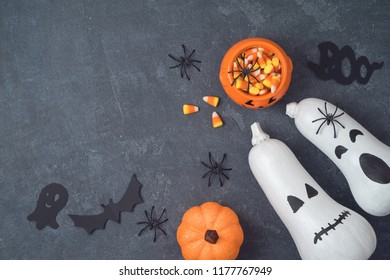 Halloween holiday concept with jack o lantern pumpkin, candy corn and decorations on black background. View from above. Flat lay
