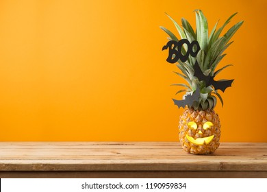 Halloween holiday concept with jack o lantern pineapple on wooden table with copy space