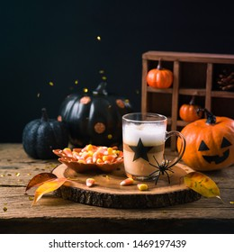Halloween holiday concept with latte macchiato cup, candy corn  and pumpkin decoration on wooden table