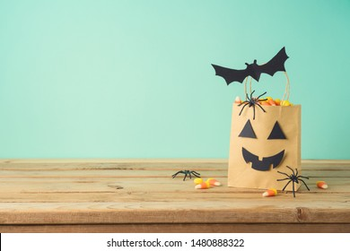 Halloween holiday concept with party gift paper bag decor and candy corn  on wooden table