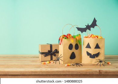 Halloween holiday concept with party gift paper bags decor and candy on wooden table