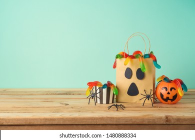 Halloween holiday concept with party gift paper bag decor and candy on wooden table