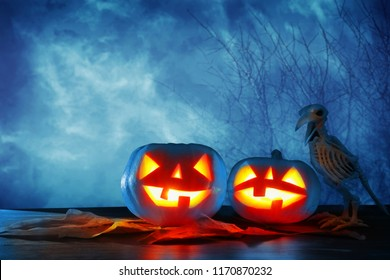 halloween holiday concept pumpkins over wooden table at night scary haunted and misty forest