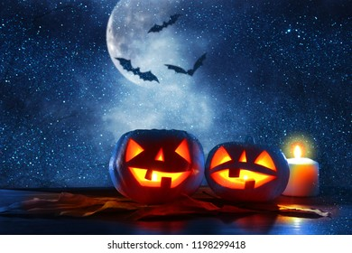 Halloween holiday concept. Pumpkins over wooden table at night scary, haunted and misty forest