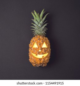 Halloween holiday minimal concept with jack o lantern pineapple. View from above. Flat lay