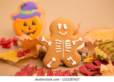 Halloween holiday - traditional sweets. Gingerbread skeleton man and pumpkin with a smile on the background of autumn leaves and kraft paper. Background image for inserting text.