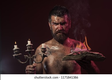 Halloween holidays celebration. Hipster man with book and candles burning on purple background. Magic spell, enchantment, witchcraft. Wizard, sorcerer, warlock. Might, mystic knowledge