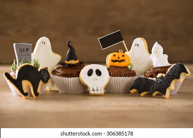 Halloween homemade gingerbread cookies and cupcakes background