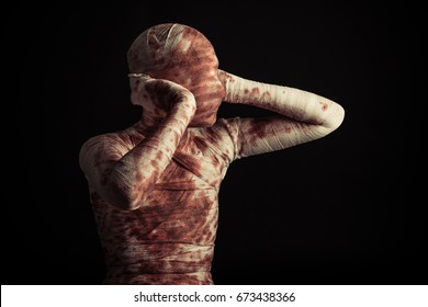 Halloween horror with a bloodstained bandaged mummy or accident victim standing holding its ears on a black background with copy space