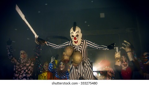 Halloween horror clowns party. Terrifying clown on stilts holding a chain with the severed heads zombie and sword.
