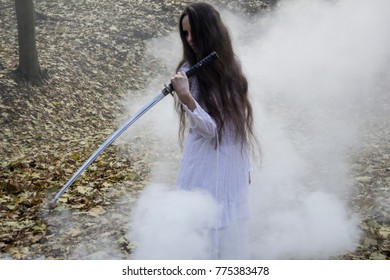 Halloween horror composition. Scaring dark haired girl in white dress with sword in the smoke and fog walking in the forest. Gothic darkness, ghost in the fog.