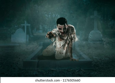 Halloween horror concept. Picture of male ghost crawling out of his grave. Shot at night time