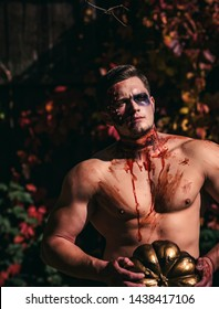 Halloween or horror concept - screaming walking dead zombie. Naked man holding creepy carved halloween pumpkin. Bloody nude man with head injury, bloody theme. Skull make up portrait of young man