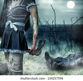 Halloween horror concept. Woman zombie holding axe in hands. In the background lies the  legs of corpse man