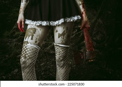 Halloween horror. Dirty woman's hand holding a bloody ax outdoor in forest