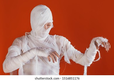 Halloween image, mummy in bandages, risen dead legendary character. young woman in the form of a mummy wrapped in bandages, on a bright orange background