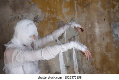 Halloween image, mummy in bandages, risen dead legendary character. Scary mummy came, nightmares and horror movies. Background textured shabby old wall
