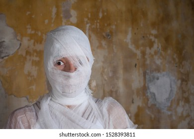 Halloween image, mummy in bandages, risen dead legendary character. young woman is mummy in shock, wrapped in bandages, against the textured old wall, copy space on the right