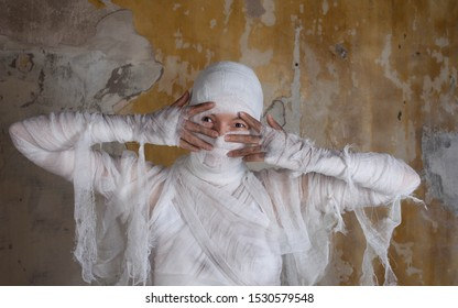 Halloween image, mummy in bandages, risen dead legendary character. Cute mummy makes funny gestures, funny concept-Happy Halloween