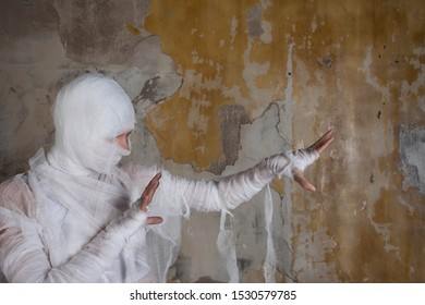Halloween image, mummy in bandages, risen dead legendary character. young woman in the form of a mummy wrapped in bandages, against the textured old wall, copy space on the right