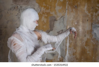 Halloween image, mummy in bandages, risen dead legendary character. young woman in the form of a mummy wrapped in bandages, against the textured old wall