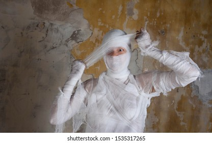 Halloween image, mummy in bandages, risen dead legendary character. Scary mummy tearing his bandages, nightmares and horror.