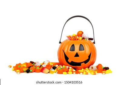 Halloween Jack o Lantern bucket overflowing with candy, side view isolated on a white background