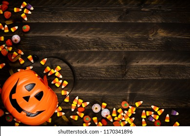 Halloween Jack o Lantern pail with corner border of spilling candy. Above view on a rustic wood background with copy space.