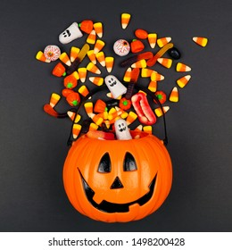 Halloween Jack o Lantern pail with spilling candy, top view on a black background