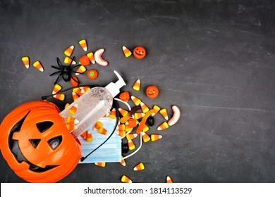 Halloween Jack o Lantern Pagel mit ausgiebigen Süßigkeiten und Vorräten für Koronavirus. Über der Aussicht auf schwarzem Hintergrund.