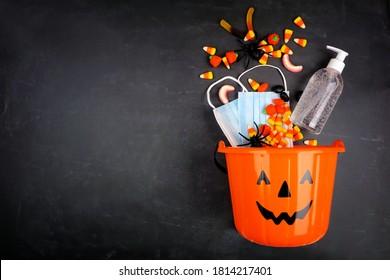 Halloween Jack o Lantern Pagel mit ausgiebiger Süßigkeiten und COVID 19 Präventivmaterial. Draufsicht auf schwarzem Hintergrund.