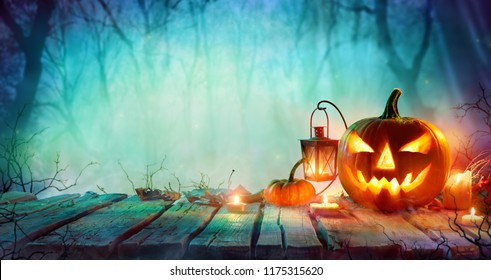 Halloween - Jack O Lanterns And Candles On Table In Misty Night