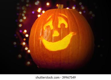 Halloween Jack-o-lantern in front of purple and orange lights.