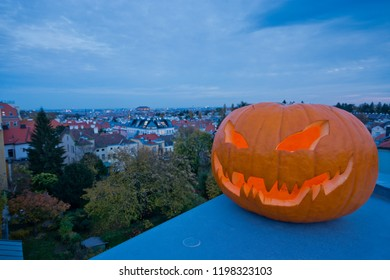 Halloween jack-o'-lantern with spooky face creates scary evening mood. Clear view to the cityscape of Vienna from the rooftops of the suburbs with city lights in the background. (Focus on pumpkin)