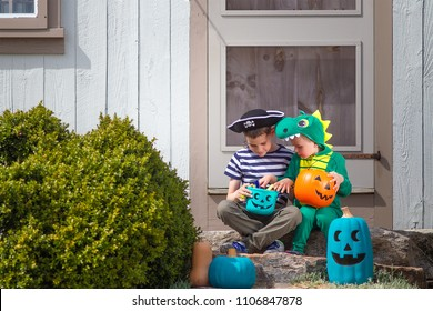 Halloween kids sitting on porch trick or treating.  Teal Pumpkin Project. Alternative non-food treats for kids with food allergies. the concept of health for children in the Halloween season.