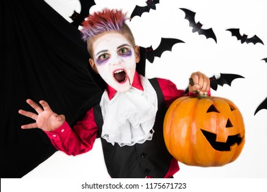 Halloween kids. Spooky Boy with a halloween costume of a vampire Dracula with halloween pumpkin jack o lantern, ready for halloween party or pumpkin patch