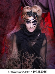 Halloween Lady. Portrait of young woman in black with artistic makeup and hairstyle.