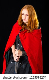halloween lass wearing in black long gown and red mantle standing with longsword, on dark background