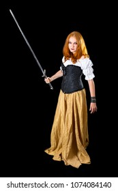 halloween lass wearing in white blouse, gold long skirt and black corset standing with longsword, on dark background