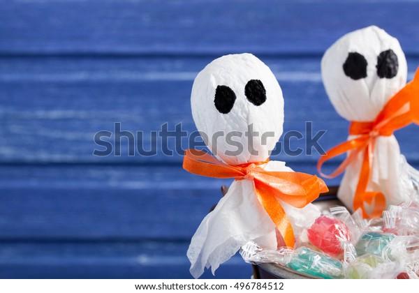 Halloween lollipop ghosts and candies on purple wooden backround, horizontal orientation