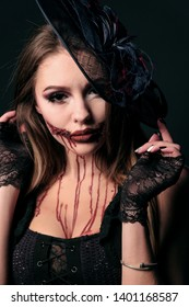 Halloween makeup, horror party costume. Portrait of a sexually beautiful girl in a scary zombie image with a bloody mouth. Black witch hat, lace gloves, red smudges on a woman's face.