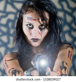 Halloween make-up on the face of a brunette girl with long hair close-up on a gray background in the studio. Girl in the image of a zombie witch with a gun in her hands.